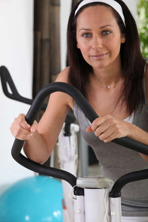 Brunette in gym using stepper machine photo