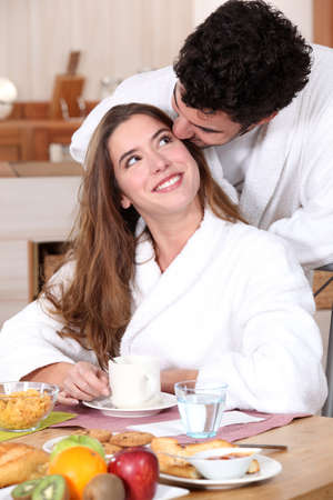 Couple wearing matching bathing robes in kitchen photo