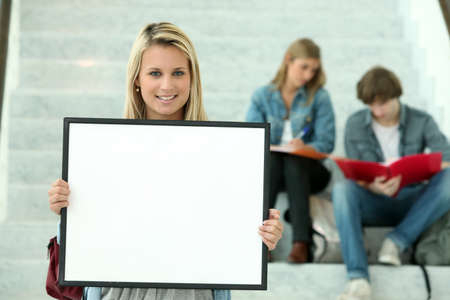 17 19 years: Girl holding a white board with students sitting in the background