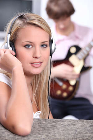 played: Young woman listening to the music being played by a guitarist sitting behind her.
