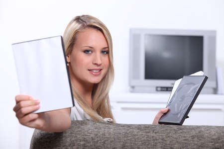 blu: Young woman choosing a DVD with a case left blank for your message