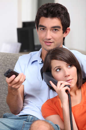 loosen up: Couple relaxing in front room at home