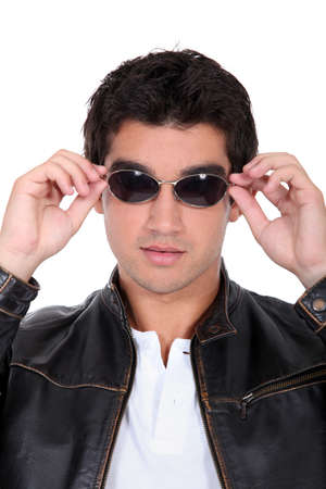 handsome man wearing leather jacket and sunglasses photo