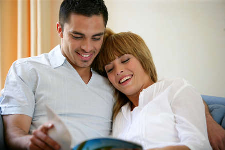 Happy couple reading a magazine on a sofa Stock Photo - 11602988