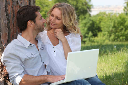 Couple with a laptop outside photo