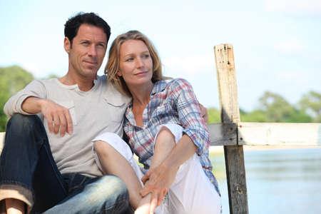 jeune vieux: Couple de d�tente sur un ponton Banque d'images