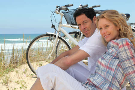 Couple with bikes sitting on the sand dunes photo
