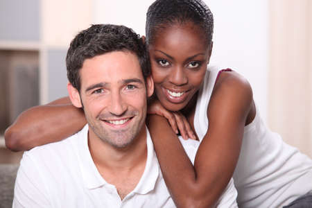 mixed couple: Landscape portrait of a mixed race couple indoors Stock Photo