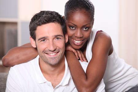 pareja en casa: Paisaje retrato de una pareja de raza mixta en el interior Foto de archivo