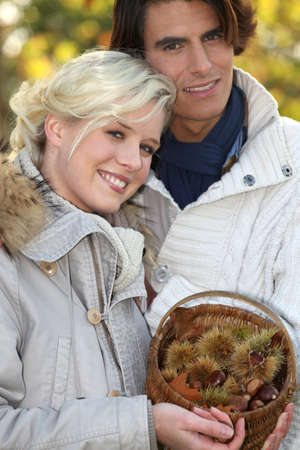 backwoods: couple dressed in warm clothes,  woman is holding a wickerwork basket full of chestnuts