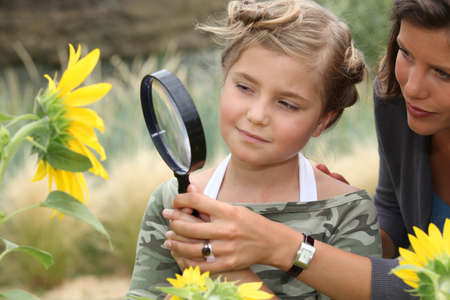 curious: Mother and daughter looking at a sunflower with a magnifying glass
