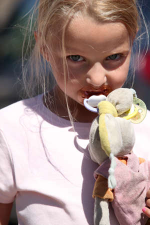well loved: Little girl with a pacifier and a dirty toy bunny