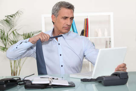 50 55: Man undoing his tie at the end of the day Stock Photo