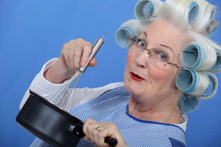 Cheeky older woman in rollers whisking sauce photo