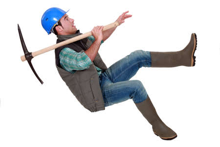 Man with pick-axe falling off chair photo
