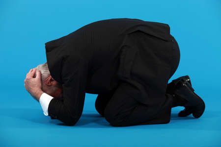 aghast: Businessman huddled on the floor