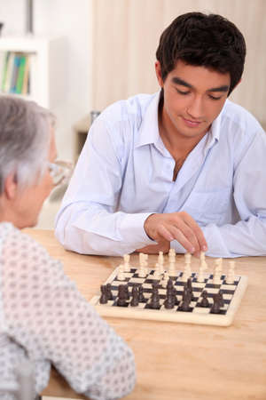 two people with others: People playing chess Stock Photo