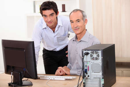 grandparent: a young man and a senior man behind a computer Stock Photo