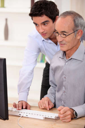younger man: Elderly man learning computer skills