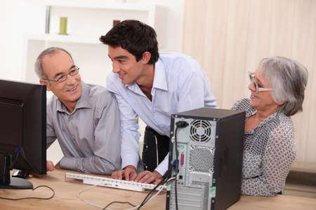 amabilidad: pareja de ancianos en frente de una computadora Foto de archivo