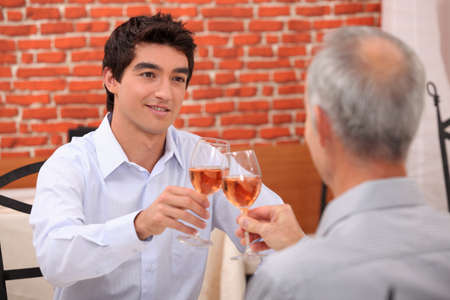 acknowledgment: Young man and senior chinking wine glasses