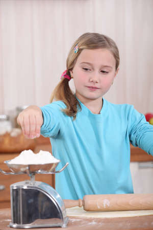 baking ingredients: Child weighing flour on a scale