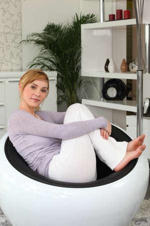 descalza: Adolescente se relaja en una silla moderna Foto de archivo