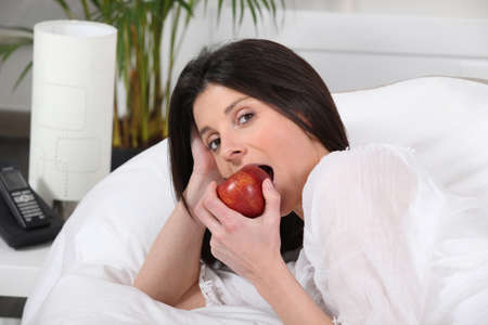 Woman eating apple in bed photo