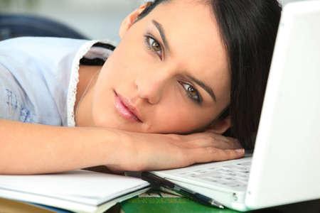 struggling: Girl falling asleep next to laptop computer