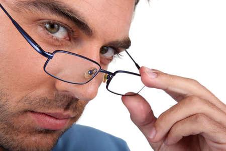 peering: Man peering over his glasses