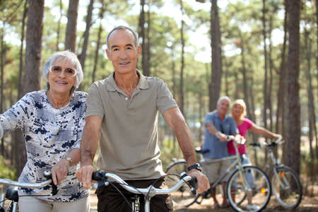 four senior people doing bike in a pine forest photo