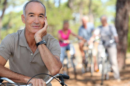 Senior on a bike with friends in the background photo