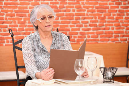 Senior woman reading menu at the restaurant photo