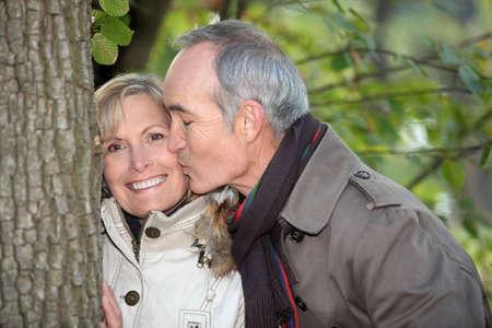 mujeres ancianas: Hombre mayor besar a su pareja bajo un �rbol Foto de archivo