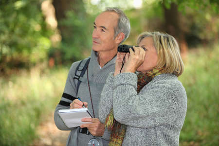 couple of retirees observing wildlife with binoculars in forest photo