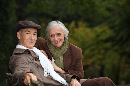 Elegant elderly couple sitting on a park bench photo