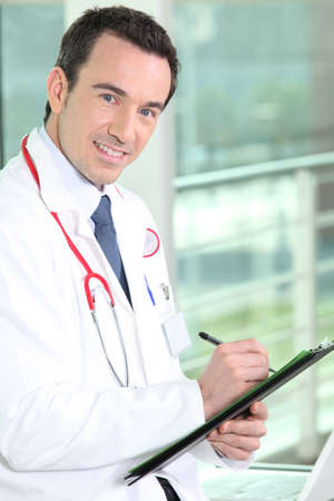 oncologist: Smiling practitioner writing on medical record Stock Photo