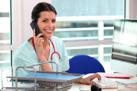 pacientes: enfermera contestando al teléfono Foto de archivo