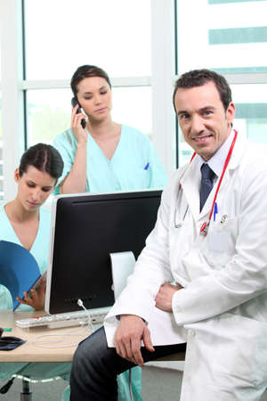 35 years old: Doctor sitting with nurses at a computer