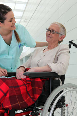 Nurse talking to an elderly lady in a wheelchair photo