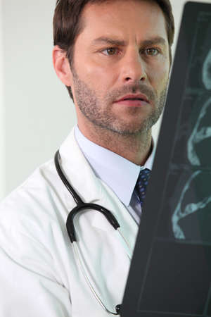 preoccupied: A worried doctor examining medical radios. Stock Photo