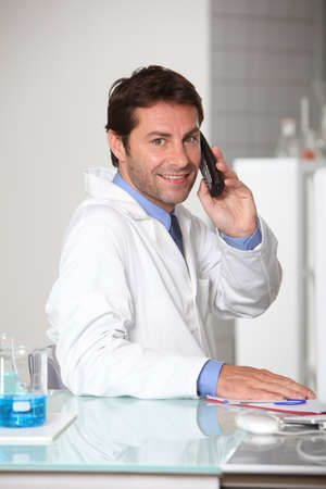 tecnico laboratorio: Sonriendo t�cnico de laboratorio en el tel�fono Foto de archivo
