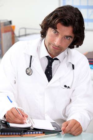 Handsome hospital doctor writing in a personal organizer