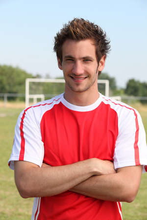 Grinning footballer with goal in the background Standard-Bild