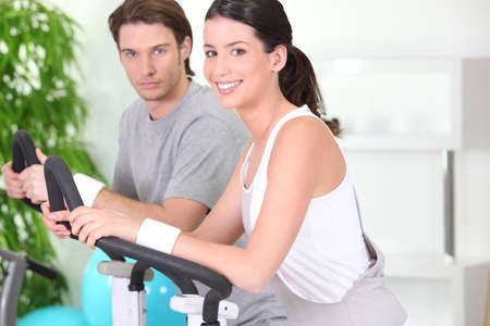 Young couple using gym equipment photo
