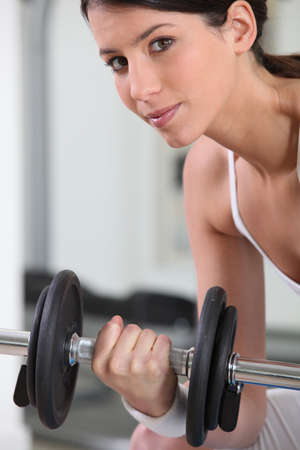 Woman lifting weights in the gym photo