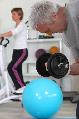 Older couple working out in gym photo
