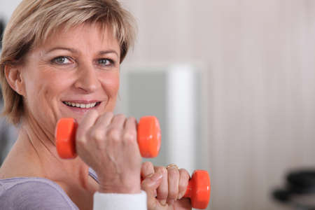 old age home: Mature woman using dumbbells