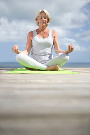 Senior woman doing yoga exercises photo