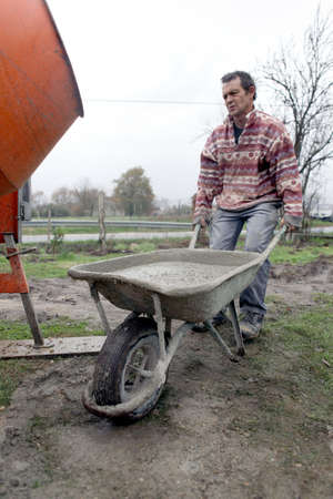 Man transporting cement in wheelbarrow photo